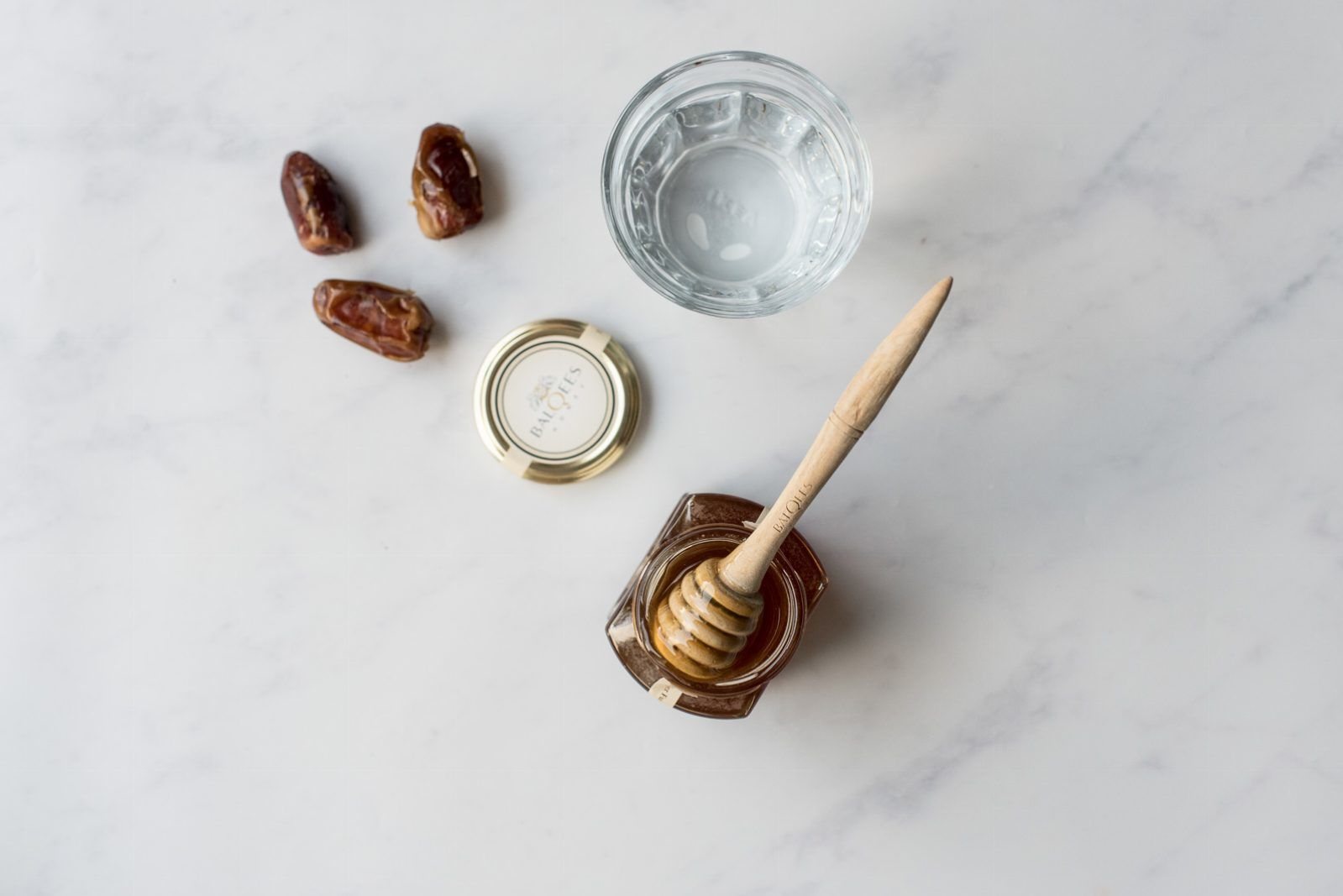 jar of honey, glass of water and dates
